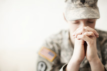 Female soldier in uniform praying.