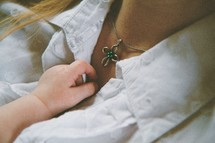 baby reaching for mother's necklace