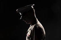 Marine soldier in uniform bowing his head in prayer.
