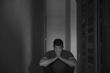 a man sitting in a dark hallway covering his face