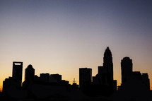 Silhouette of city skyline at sunset.