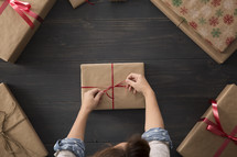 Wrapping gifts in brown paper and red ribbon.
