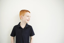 A smiling red-headed boy.