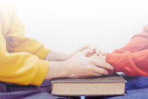 a couple holding hands and praying over a Bible