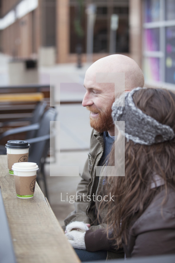 Couple sitting outside with coffee.