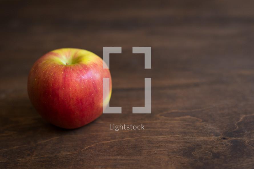 apple on a wood desk