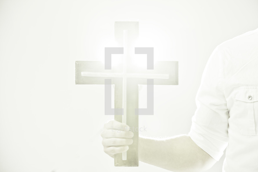 hand holding a glowing cross