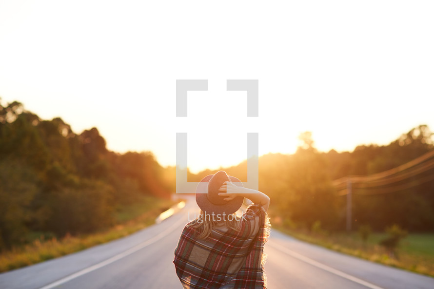 a woman in a hat walking down a country road