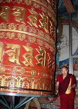 A Tibetan man sends prayers spiralling up to heaven by spinning a Buddhist prayer wheel in Nepal, Asia