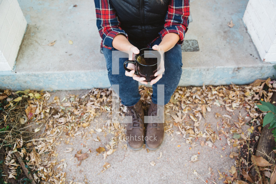 woman sitting on a stoop holding a mug of tea