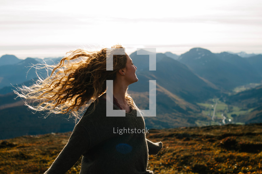 a joyous woman dancing on a mountaintop
