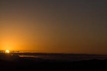 sun setting over mountain peaks