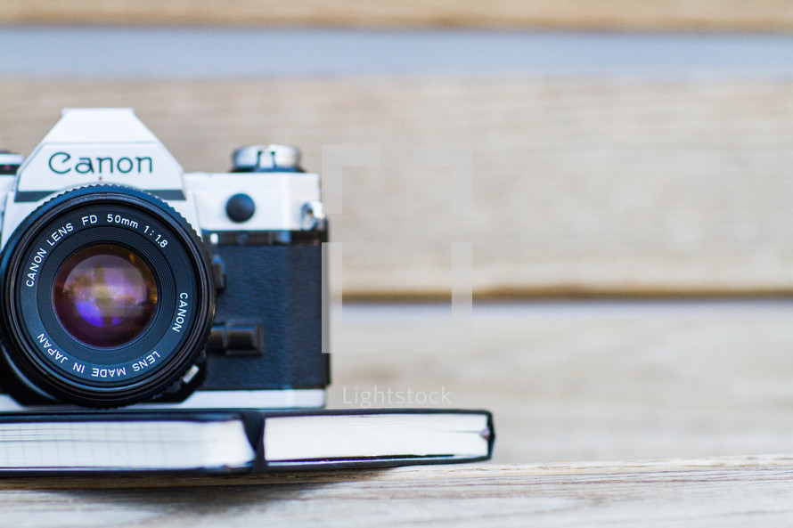 A camera and book on a table.