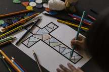 a child coloring a cross