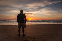 A man standing on a beach and watching the sun set over the ocean.