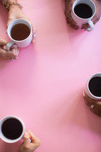 The hands of four women holding coffee cups on a pink table.