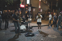street musicians performing on a street corner at night