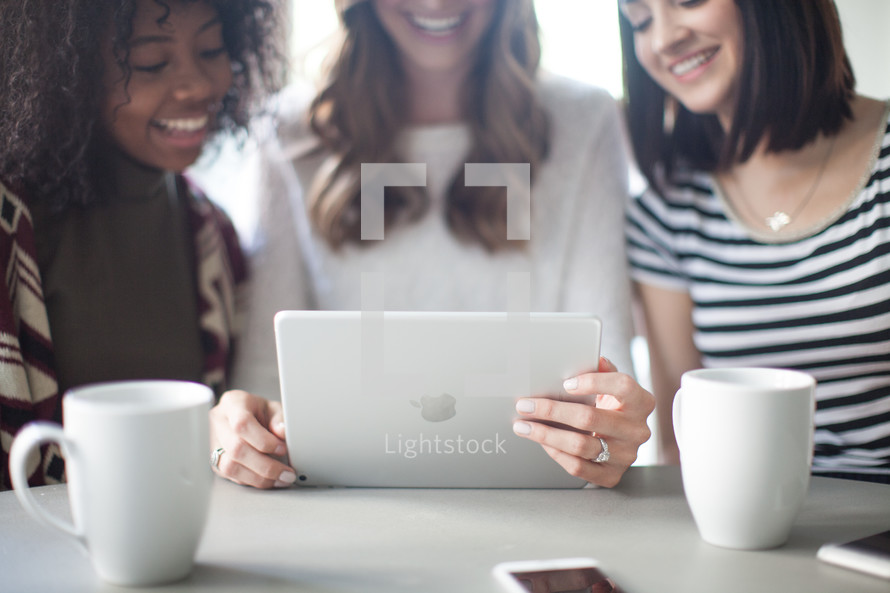 Three young women sitting at a table and looking at an electronic tablet.