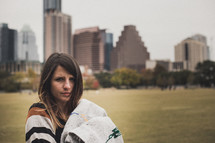 woman wrapped in a blanket standing in a park in a city