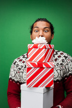 a man holding a stack of Christmas gifts