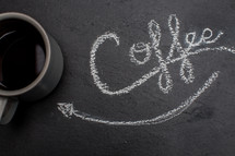 word coffee in chalk and an arrow pointing to a coffee mug