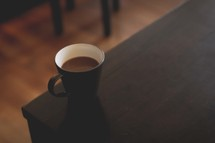 a coffee cup at the edge of a table