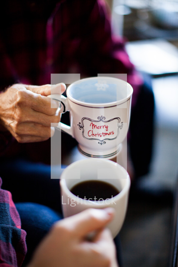 Hands holding coffee mugs that say Merry Christmas