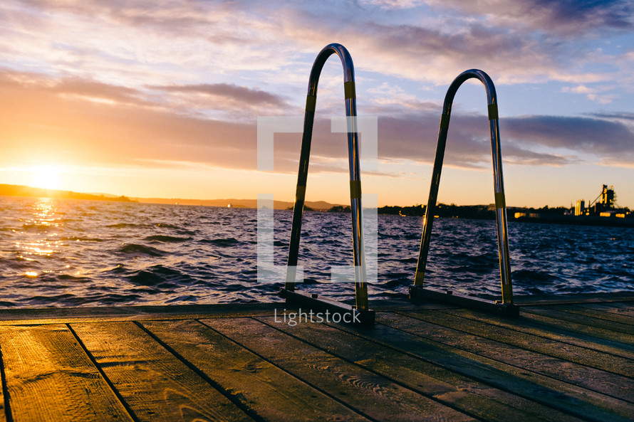 ladder on a floating dock at sunset