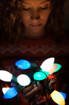 a woman holding a string of Christmas lights in darkness