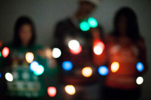 friends holding glowing Christmas lights