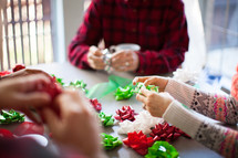 People wrapping Christmas presents around a table