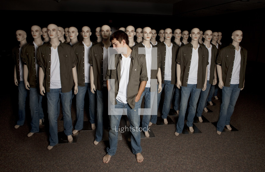 man standing with manikins blending in