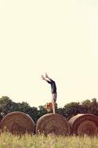 woman doing a handstand on bales of hay