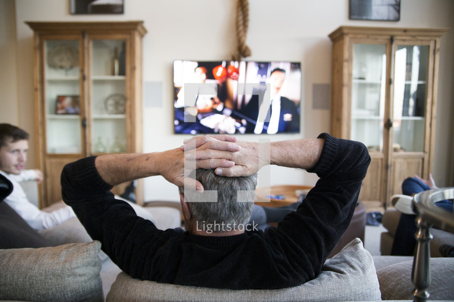 men sitting on a couch watching tv