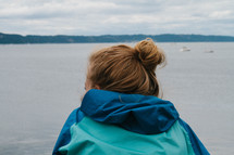 a teen girl looking out at lake water