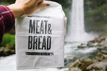 meat and bread paper sack near a waterfall