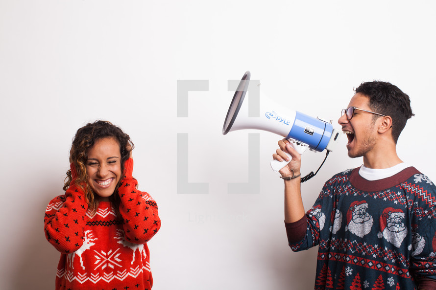 man in an ugly Christmas sweater yelling into a megaphone