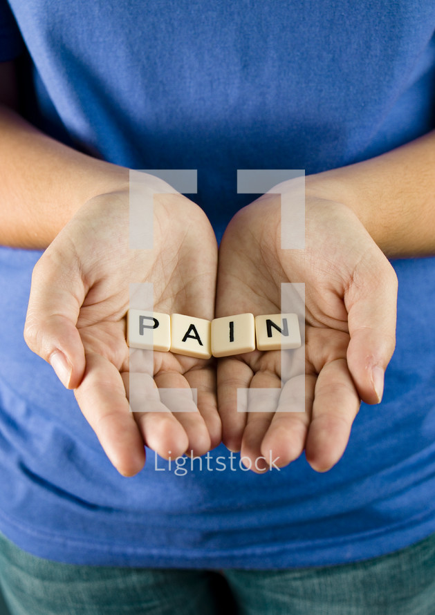 "A young girl holds out the word ""PAIN"""