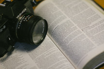 a camera on the pages of a Bible