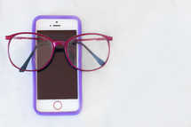 Red reading glasses on a cellphone on a solid white background.