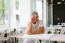 a man sitting alone at a table in a diner
