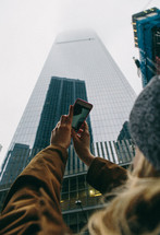 woman taking a picture of a skyscraper with her phone
