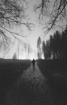 man walking on a muddy path in fog