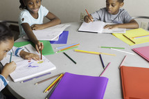 kids coloring around a table