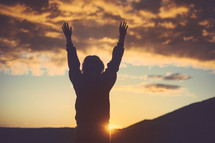 silhouette of a woman with raised hands at sunset
