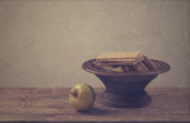 bowl of crackers and an apple