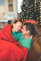 a couple snuggling under a blanket at Christmas