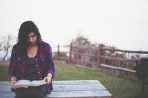 Woman reading the Bible while sitting on an outdoor picnic table.