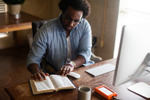 An African American man sitting at a desk near a computer and reading a Bible