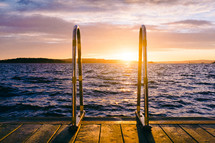 Sunset over water with a wooden dock and a ladder.